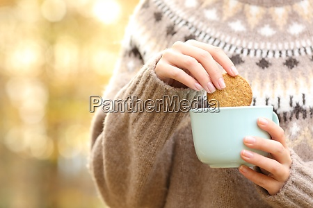 woman dipping cookie in a coffee