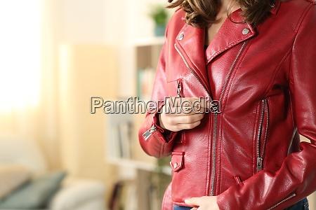 woman hands closing zipper of red