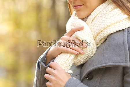 woman hands putting on a scarf