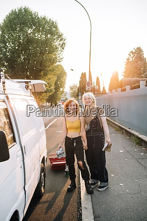 young lesbian couple beside their van