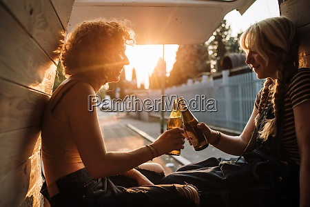 young female couple toasting with beer