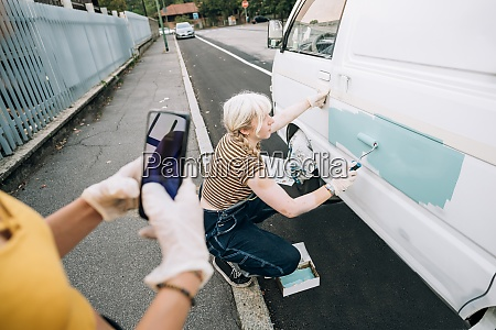 woman photographing girlfriend as she paints