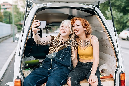 lesbian couple smiling and taking selfie