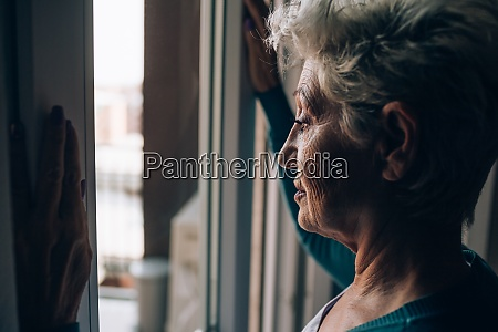 senior woman looking out from apartment
