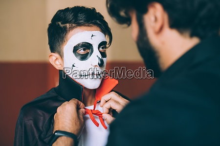 father adjusting sons halloween costume