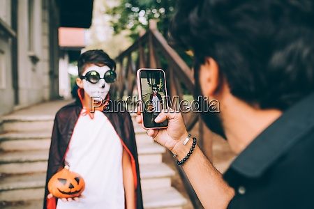 father photographing son in halloween costume