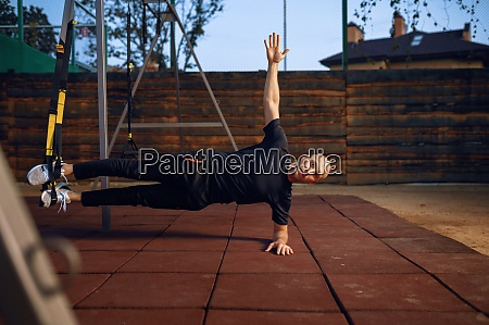 sportive man doing balance exercise outdoors