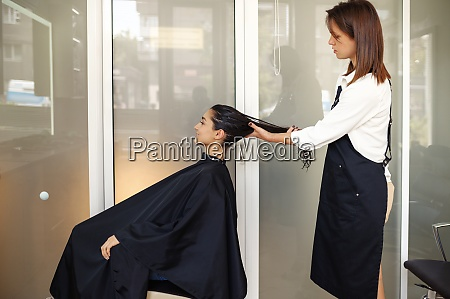 hairdresser holds womans hair hairdressing salon