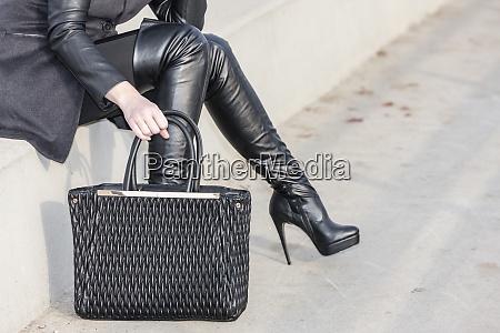 fashionable black boots with a handbag