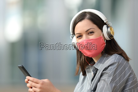 happy woman with mask and headphones