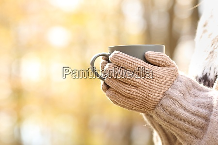 woman hands with gloves holding coffee