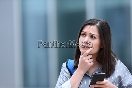 worried student holding phone thinking looking