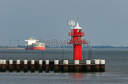 lighthouse with cargo ship in the
