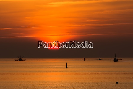 silhouette of fishing trawlers on the