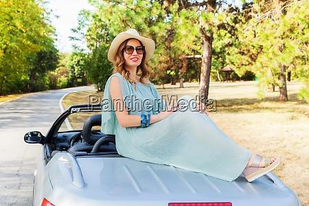 attractive woman posing at convertible car