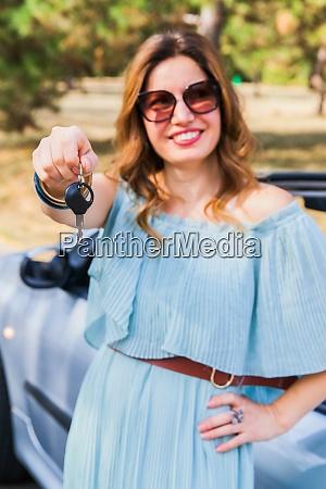 portrait of smiling woman showing car