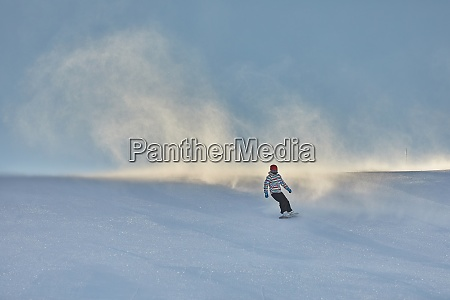 female snowboarder fast on a slope