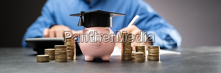 college piggy bank with graduation hat