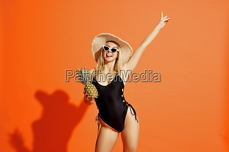 woman in swimsuit poses with pineapple