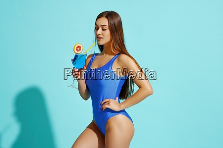 woman in swimsuit poses with coctail