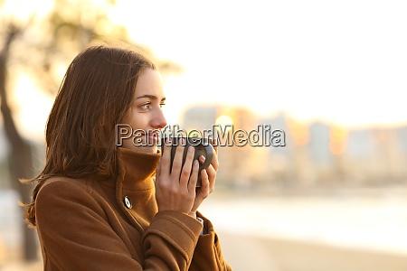 woman drinking coffee on the beach