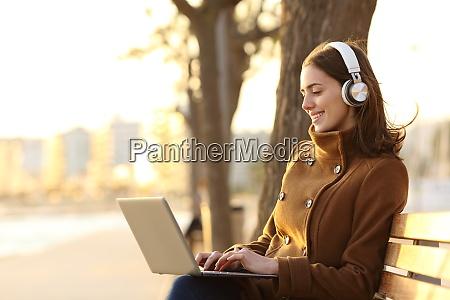 woman wearing headphones using laptop in