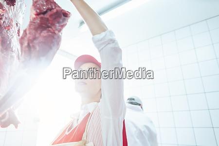 butcher woman taking meat from hook