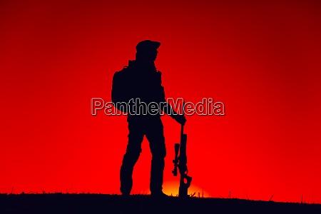 elite forces sniper patrolling with gun