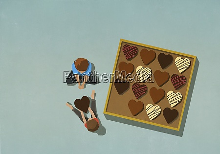 man giving heart shape chocolate to