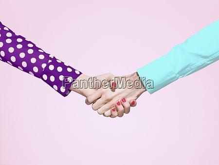 vibrant handshake on pink background
