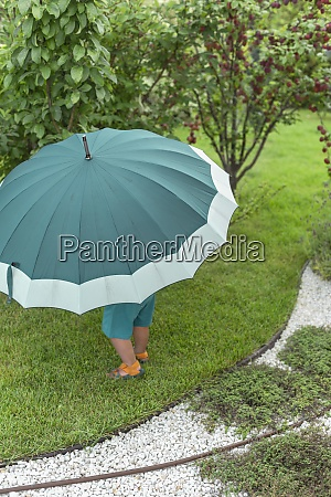 toddler under large green umbrella in