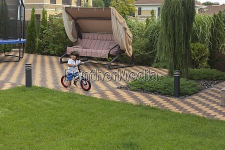 carefree toddler boy riding bicycle in