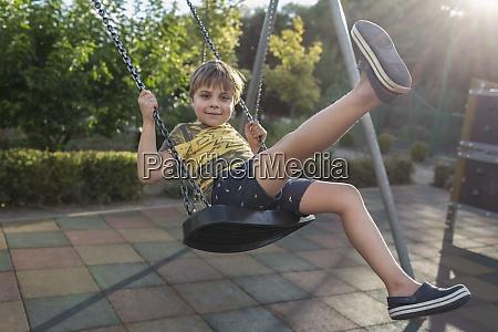 portrait carefree boy swinging at sunny