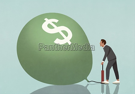 businessman inflating dollar sign balloon with