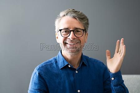 smiling man waving hello