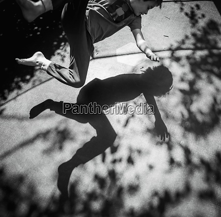 shadow of boy jumping on sunny