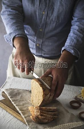 man slicing fresh home baked sourdough