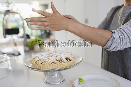 woman dusting homemade pie with powdered