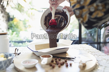 woman pouring brownie batter into baking