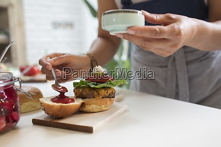 close up woman spreading ketchup on