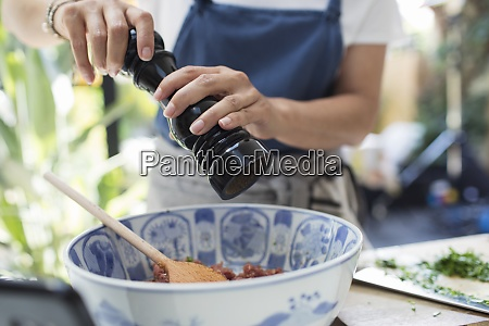 close up woman with pepper grinder