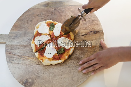 woman slicing fresh homemade pizza on