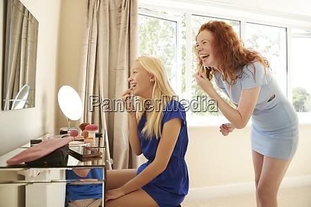 happy preteen girl friends applying makeup