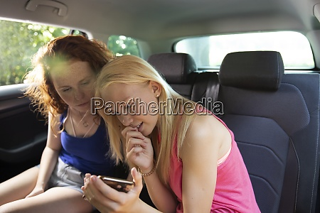 preteen girl friends using smart phone