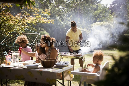 family barbecuing and eating on sunny