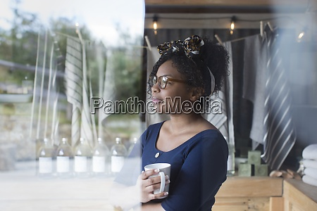 thoughtful female shop owner drinking coffee