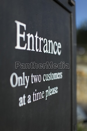 social distancing sign at shop entrance