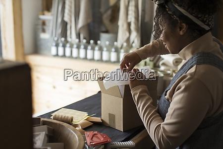 female shop owner preparing package at