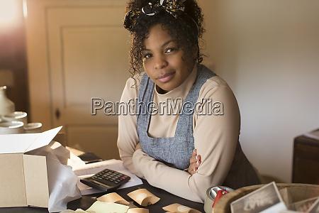 portrait confident female shop owner packaging