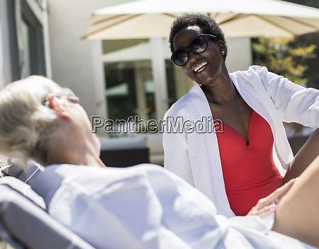happy senior women friends sunbathing on